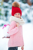 在冰溜冰场的可爱的小女孩去的冰鞋在冬天雪天 免版税图库摄影
