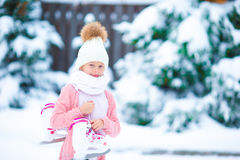 在冰溜冰场的可爱的小女孩去的冰鞋在冬天雪天 库存图片