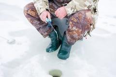 在冰的冬天捕鱼 伪装制服的渔夫坐在冰的一个箱子,拿着冬天渔的渔冰标尺,低 库存照片