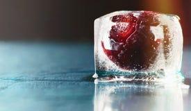 在冰的冷冻可口红色樱桃在藏青色背景 免版税库存照片