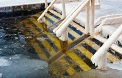 在冰的孔在突然显现沐浴的冬天森林 免版税图库摄影