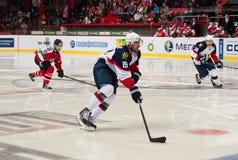 在冰的曲棍球从向前米谢尔Miklik防御者弗拉基米尔Migalik Slovan (布拉索夫)和弗雷德里克特森Donbass ( 图库摄影