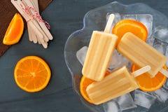 在冰的橙色酸奶冰棍儿填装了碗 免版税库存照片