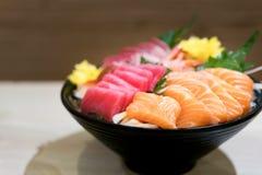 在冰的混杂的切的鱼生鱼片在黑碗 生鱼片三文鱼T 免版税库存图片