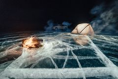 在冰的火在晚上 在冰的营地 帐篷在篝火旁边站立 贝加尔湖湖 附近有汽车 军中两人用帐篷和 免版税库存图片