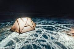 在冰的火在晚上 在冰的营地 帐篷在篝火旁边站立 贝加尔湖湖 附近有汽车 军中两人用帐篷和 库存图片