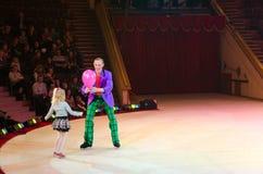 在冰的莫斯科马戏在游览中 有气球和小女孩的小丑 库存照片