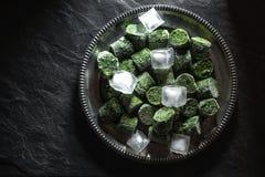 在冰砖的冷冻在一块板材的菠菜和冰在桌的中心 免版税库存照片