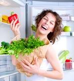 在冰箱妇女年轻人附近的饮食 库存照片
