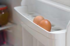 在冰箱门的架子的两个鸡鸡蛋打开closeu 免版税库存照片