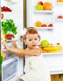 在冰箱附近的愉快的小女孩用健康食物,果子和 免版税库存图片