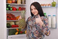 在冰箱附近的美丽的女孩用健康食物 库存照片