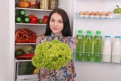 在冰箱附近的美丽的女孩用健康食物 免版税库存图片