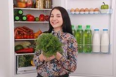 在冰箱附近的美丽的女孩用健康食物 库存图片