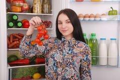 在冰箱附近的美丽的女孩用健康食物 免版税图库摄影