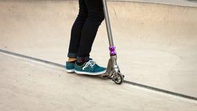 在冰鞋公园推挤滑行车男孩 免版税库存图片