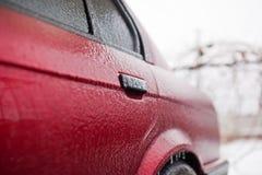 在冰结冰的红色机器在风暴以后 库存图片
