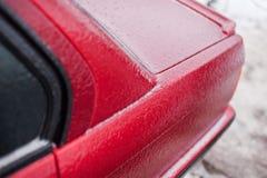 在冰结冰的红色机器在风暴以后 免版税库存图片