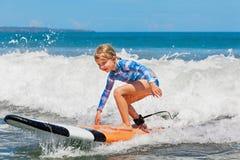 在冲浪板的年轻冲浪者乘驾有在海的乐趣的挥动 免版税图库摄影