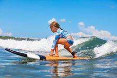在冲浪板的年轻冲浪者乘驾有在海的乐趣的挥动 库存图片