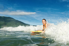 在冲浪板的美好的年轻深色的女子游泳有好的微笑的 免版税图库摄影