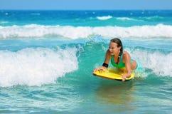 在冲浪板的年轻有吸引力的妇女bodyboards有好的微笑的 免版税库存图片