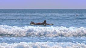 在冲浪板等待的女孩谎言在夏日挥动 股票录像