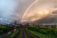 在冶金植物上的一条色的彩虹 免版税库存照片