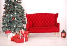 在冷杉木下的当前箱子在与红色沙发的内部 免版税图库摄影