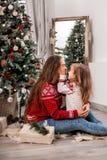 在冷杉木附近的愉快的母亲和女儿容忍 图库摄影