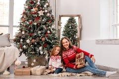 在冷杉木附近的愉快的母亲和女儿就座 免版税库存照片
