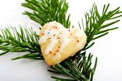 在冷杉枝杈的心形的圣诞节曲奇饼 库存照片