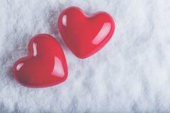 在冷淡的白色雪背景的两红色光滑的心脏 爱和圣华伦泰概念 免版税库存图片