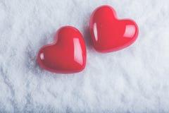 在冷淡的白色雪背景的两红色光滑的心脏 爱和圣华伦泰概念 库存图片