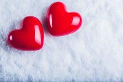 在冷淡的白色雪背景的两红色光滑的心脏 爱和圣华伦泰概念 图库摄影