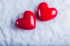 在冷淡的白色雪背景的两红色光滑的心脏 爱和圣华伦泰概念 免版税库存照片
