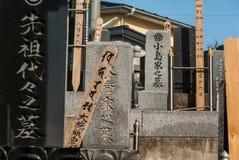 在冷漠的午间太阳的水平的取向的日本坟墓 图库摄影