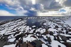 在冷的挪威海岸的古老石头晚上时间的 海岛lofoten 美丽的域前景横向挪威草莓 图库摄影