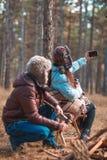 在冷的森林A女孩的一对夫妇在电话做与人的一selfie 户外 免版税库存照片