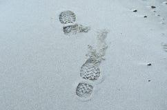 在冷的白色结冰的海滩的人的鞋子印刷品 免版税库存照片