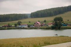 在冷的秋天天空的重的灰色云彩在有小屋的村庄很远山和领域的 一点河流程 库存图片