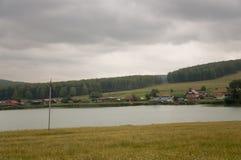 在冷的秋天天空的重的灰色云彩在有小屋的村庄很远山和领域的 一点河流程 图库摄影