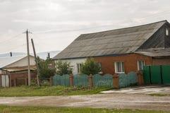 在冷的秋天天空的重的灰色云彩在有小屋的村庄很远山和领域的 旅行在s 免版税库存图片