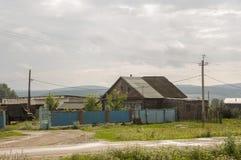 在冷的秋天天空的重的灰色云彩在有小屋的村庄很远山和领域的 旅行在s 库存照片