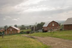 在冷的秋天天空的重的灰色云彩在有小屋的村庄很远山和领域的 旅行在s 库存图片