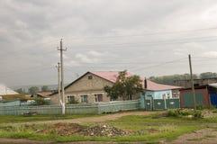 在冷的秋天天空的重的灰色云彩在有小屋的村庄很远山和领域的 旅行在s 免版税库存照片