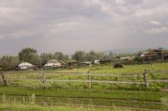 在冷的秋天天空的重的灰色云彩在有小屋的村庄很远山和领域的 旅行在s 图库摄影