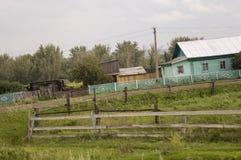 在冷的秋天天空的重的灰色云彩在有小屋的村庄很远山和领域的 旅行在s 免版税图库摄影