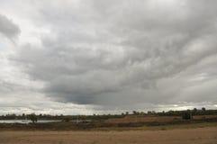 在冷的秋天天空的重的灰色云彩在河、领域、森林和山 免版税库存图片