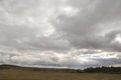 在冷的秋天天空的重的灰色云彩在河、领域、森林和山 库存图片